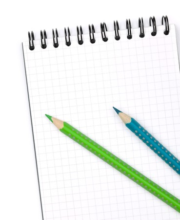 Two color pencils on notepad. Closeup. Isolated on white background photo