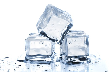 ice cubes: Three melting ice cubes on glass table. On white background Stock Photo