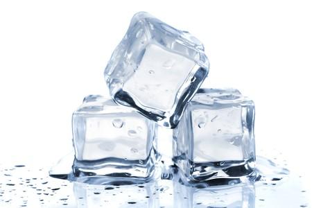 cubetti di ghiaccio: Tre cubetti di ghiaccio fusione sul tavolo di vetro. Su sfondo bianco