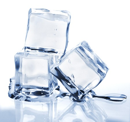 Three melting ice cubes on glass table. On white background Stock Photo