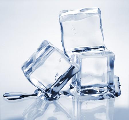 cubos de hielo: Tres cubos de hielo fusi�n sobre mesa de vidrio  Foto de archivo