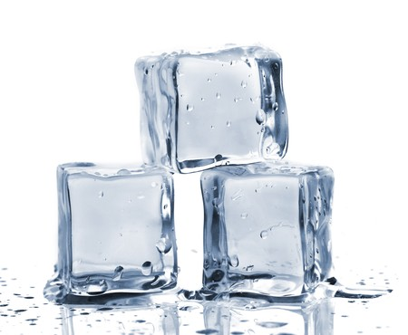 cubos de hielo: Tres cubos de hielo sobre la mesa de vidrio. Aislados en blanco