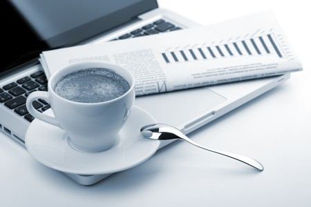 Cappuccino cup with laptop and newspaper. Blue toned photo