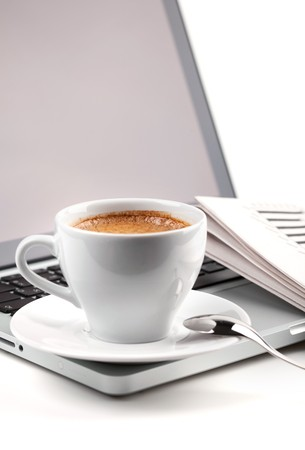 Hot cappuccino cup on laptop and newspaper. On white Stock Photo - 8169633
