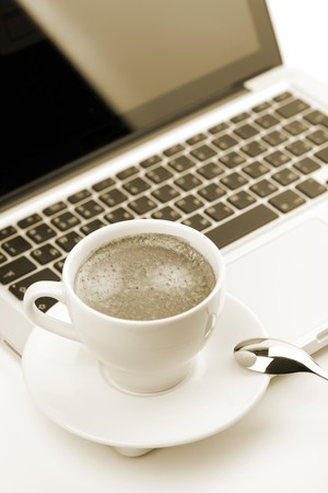 Cappuccino cup on laptop. Toned photo