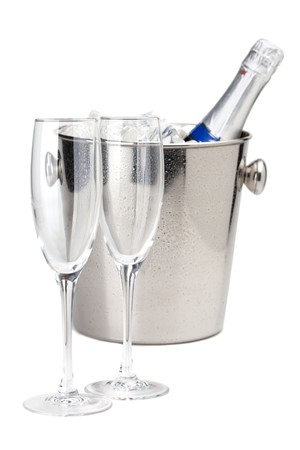 Champagne bottle in cold ice bucket and two empty glasses. Isolated on white