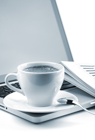 Hot cappuccino cup on laptop and newspaper. Blue toned photo