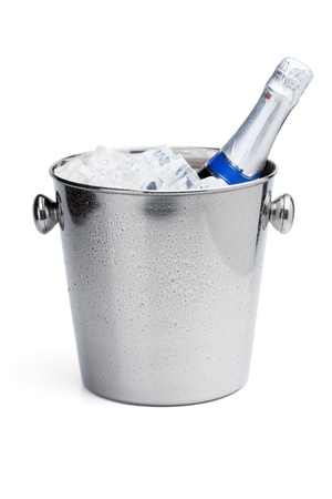 Champagne bottle in cold ice bucket. Isolated on white photo