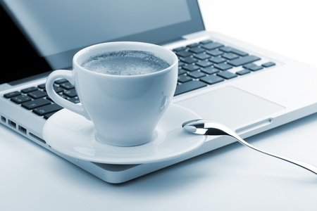 Cappuccino cup on laptop. Small DOF, blue toned photo