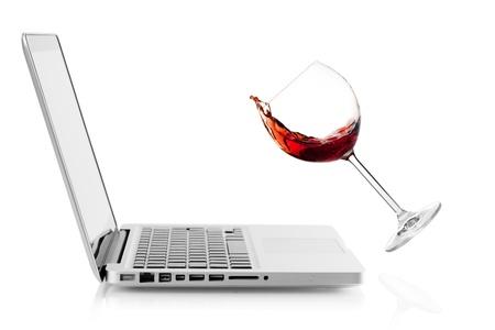 Wine falling on laptop. Isolated on white background photo