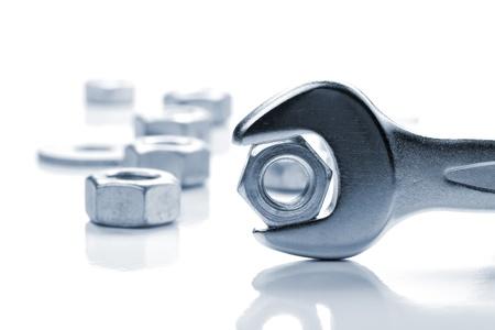 herramientas de mec�nica: Tuerca de metal en la llave. En tonos de azul Foto de archivo
