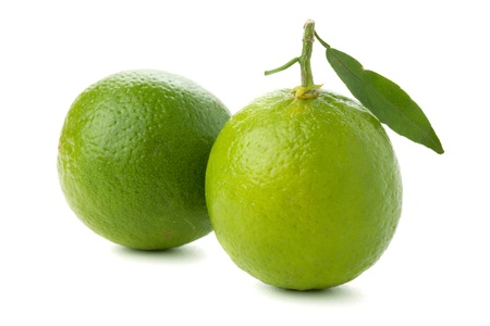 Two ripe limes with leaf. Isolated on white photo