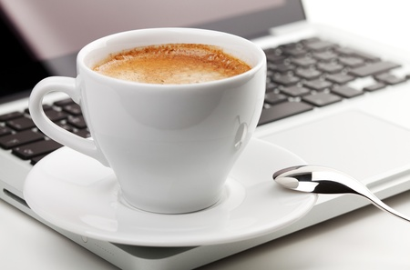 office break: Cappuccino cup with spoon on laptop. Small DOF Stock Photo