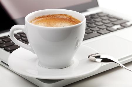office break: Taza de Cappuccino con cuchara en el port�til. DOF peque�a Foto de archivo
