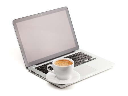 Hot cappuccino cup on laptop. Isolated on white background photo