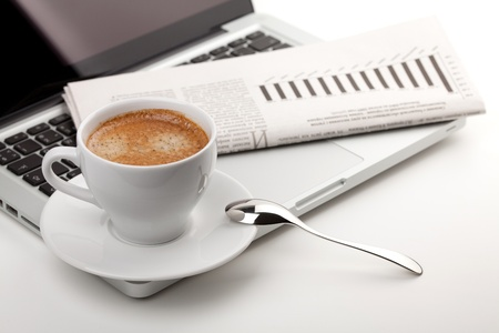 business news: Cappuccino cup with laptop and newspaper