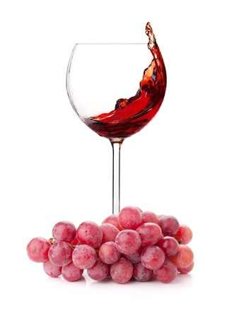 incidence: Splashing red wine in a glass and grapes. Isolated on white background Stock Photo