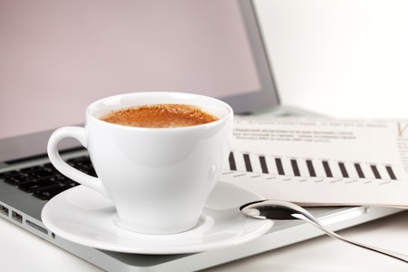 Cappuccino cup with laptop and newspaper. Small DOF Stock Photo - 9402325