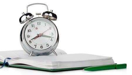 Alarm clock on notepad. Isolated on white background Stock Photo - 9559972