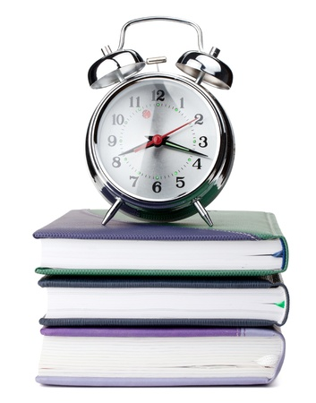 Alarm clock on notepads and books. Isolated on white background photo