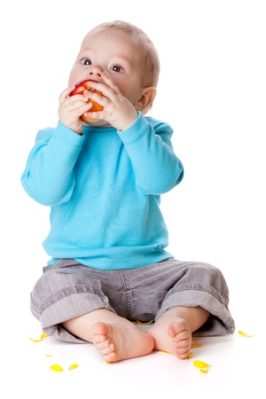 Small baby eating red apple. Isolated on white photo
