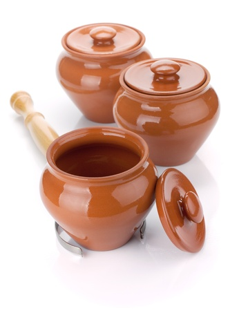 Three clay pots and holder. Isolated on white background photo