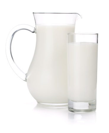 Milk jug and glass. Isolated on white background photo