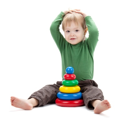 Small baby with a toy pyramid. Isolated on white background photo