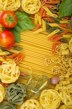 italy background: Overhead various Italian pasta background with tomatoes, basil and garlic