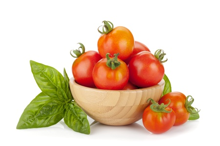 Ripe tomatoes in a bowl and basil. Isolated on white background photo