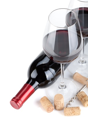 Red wine glasses, bottle and corks. Closeup. Isolated on white background photo