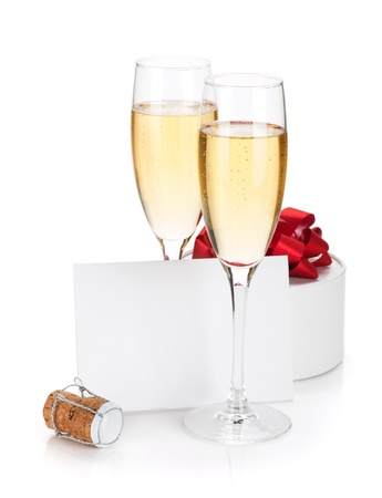 Champagne glasses, empty card and gift. Isolated on white background