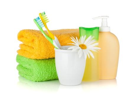 aseo personal: Cepillos de dientes, botellas de champú, dos toallas y flores. Aislado sobre fondo blanco Foto de archivo