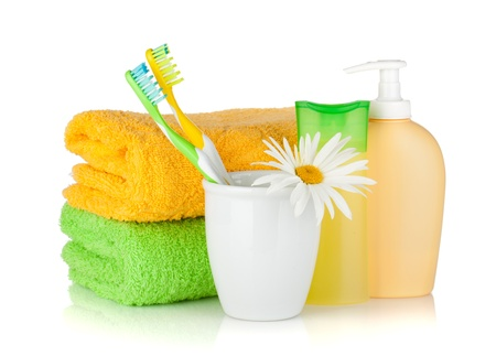 'personal beauty': Toothbrushes, shampoo bottles, two towels and flower. Isolated on white background