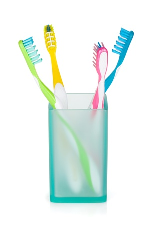 Four multicolored toothbrushes in glass. Isolated on white background photo