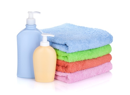 Cosmetics bottles and towels. Isolated on white background Stock Photo