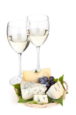 tabla de quesos: Queso, uvas y dos vasos de vino blanco. Aislado sobre fondo blanco Foto de archivo
