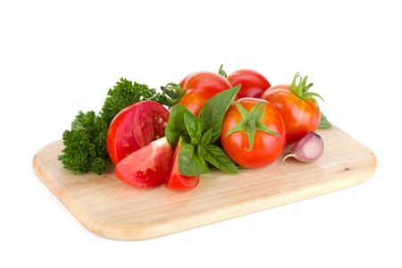 cutting vegetables: Ripe tomatoes, basil and parsley on cutting board. Isolated on white background