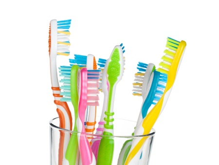 Colorful toothbrushes in glass  Closeup  Isolated on white background photo