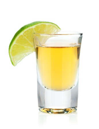 Shot of gold tequila with lime slice. Isolated on white background photo