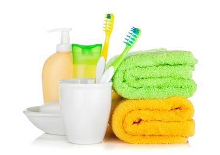 Personal Care: Two colorful toothbrushes, cosmetics bottles and towels. Isolated on white background Stock Photo