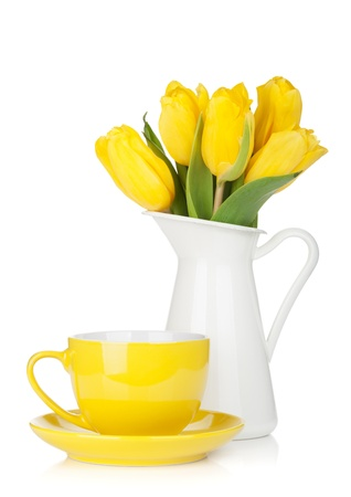 Yellow tulips and tea cup. Isolated on white background Banco de Imagens