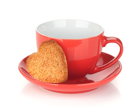 teacup: Red coffee cup and heart shaped cookie. Isolated on white background