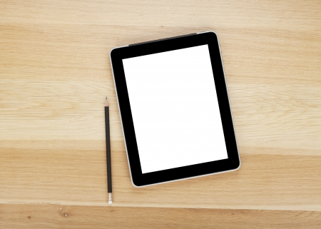 Touch screen tablet computer with blank screen and pencil on wooden table photo