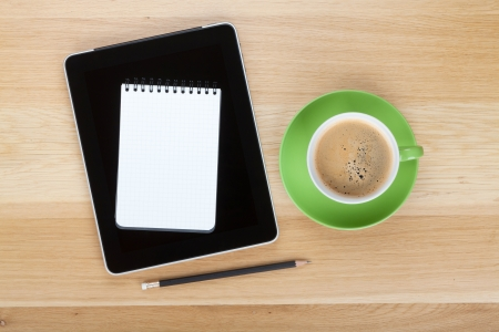 Touch screen tablet computer, notepad, pencil and cup of coffee on wooden table Stock Photo - 17744838