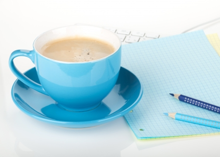 Blue coffee cup and office supplies. Closeup on white background photo