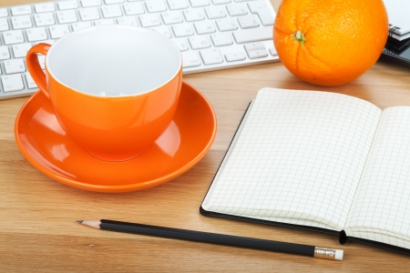 Coffee cup, orange fruit and office supplies on wooden table photo