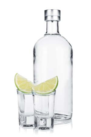 Bottle of vodka and shot glasses with lime slice. Isolated on white background