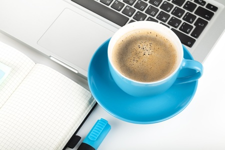 Blue coffee cup, laptop and office supplies. Closeup on white background photo