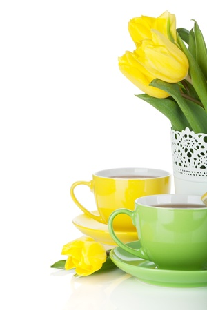 Yellow tulips and two tea cups. Isolated on white background photo